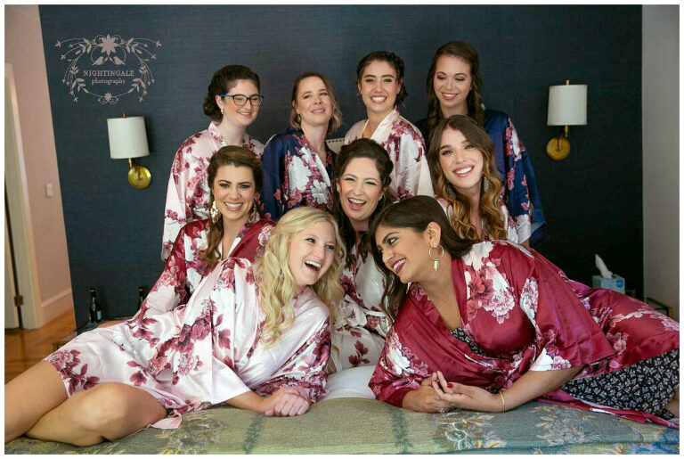 bride and her bridal party laugh on bed