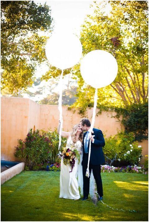 wedding photos by carmel valley elopement photof couple holding large balloons at carmel wedding venue, bernardus lodge