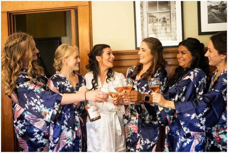 bridesmaids wear matching robes and cheers with wine before wedding