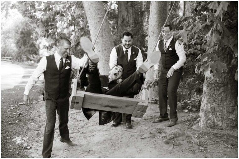 funny photo of groom on swing with groomsmen in santa barbara