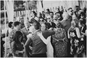 bride hugs guests after her backyard rustic wedding