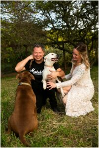 newlyweds kiss their dogs after their rustic and intimate wedding