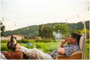 wedding guest smokes cigar in backyard at this intimate rustic wedding