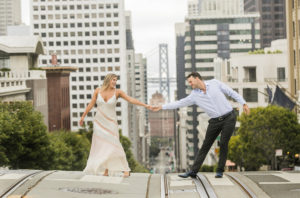 couple cross the street with views of steep streets in san francisco